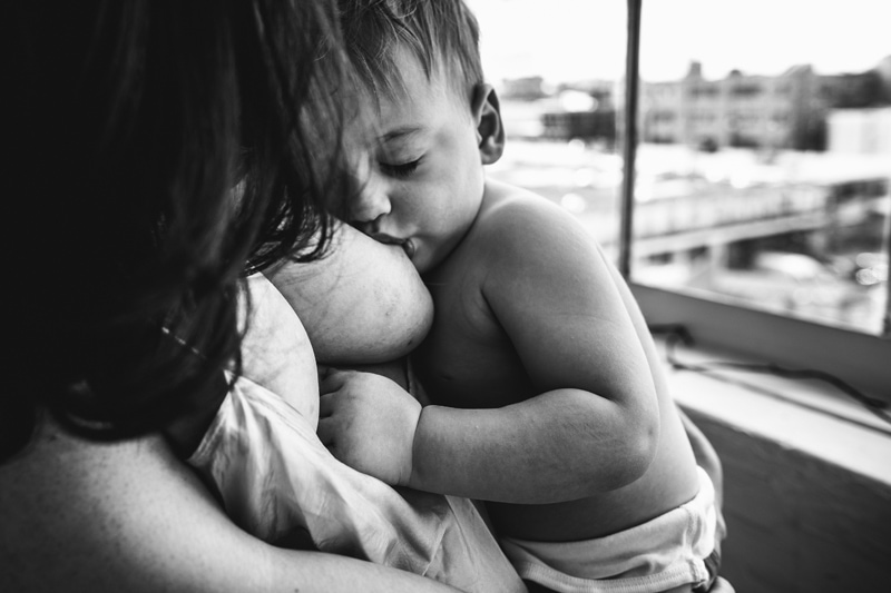 Motherhood and Maternity Photography, black and white image of young boy breastfeeding