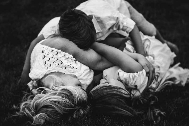 family photography, black and white of mother and children laying in the grass