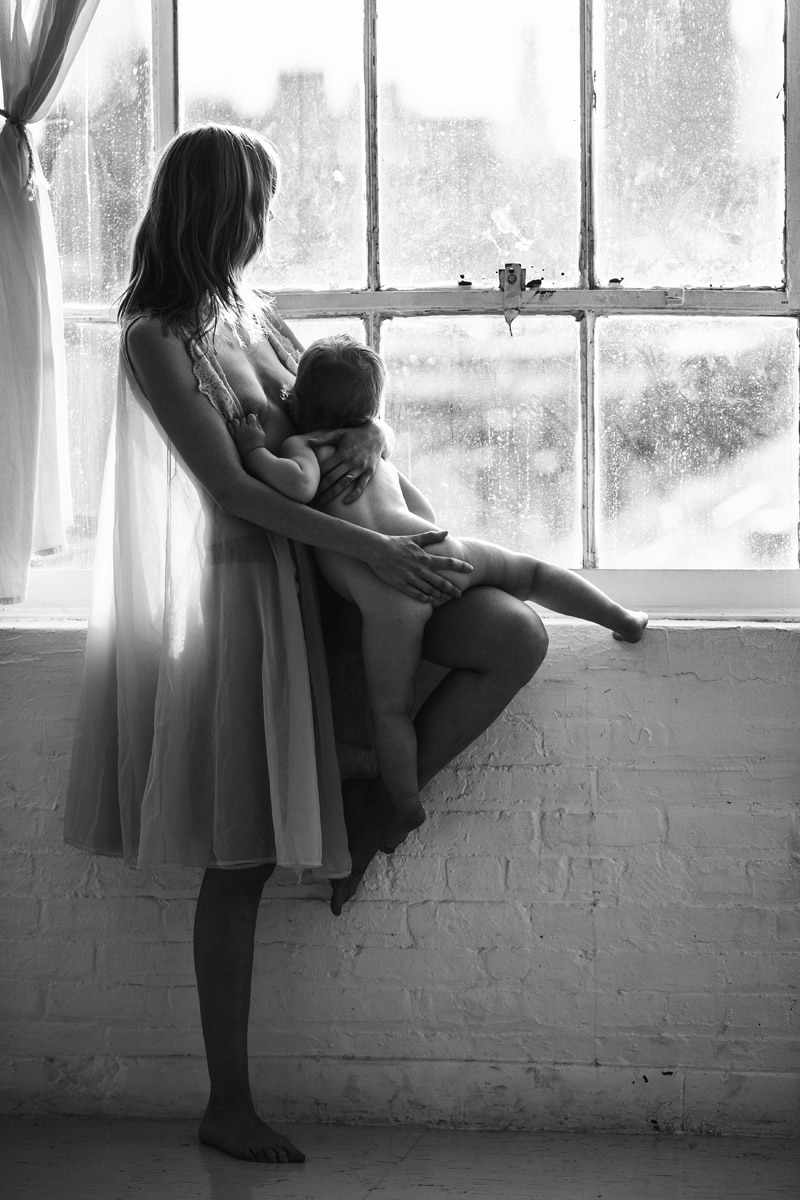Motherhood and Maternity Photography, black and white of mother breastfeeding next to a window