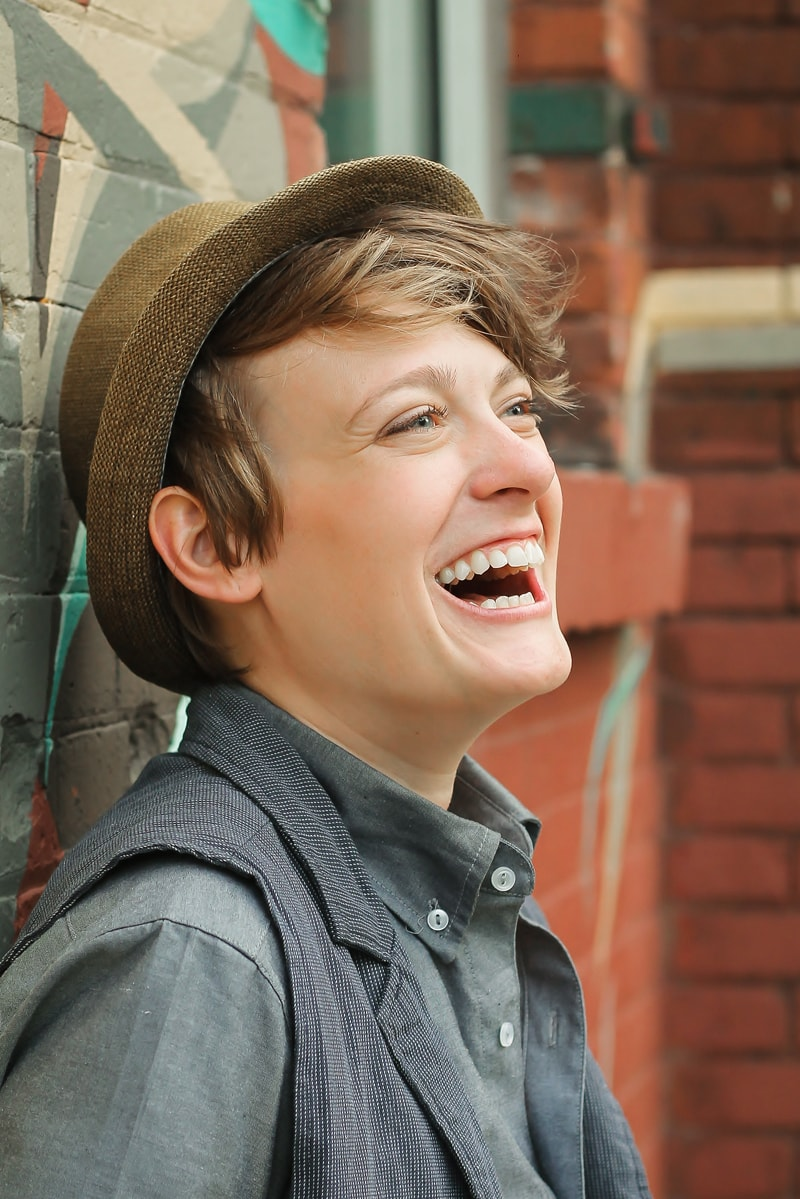 artist photography, close up of woman laughing, wearing a hat