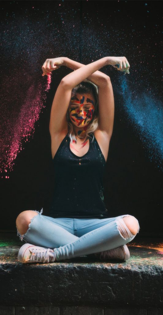 Senior Photography, young woman dropping colorful dust around herself