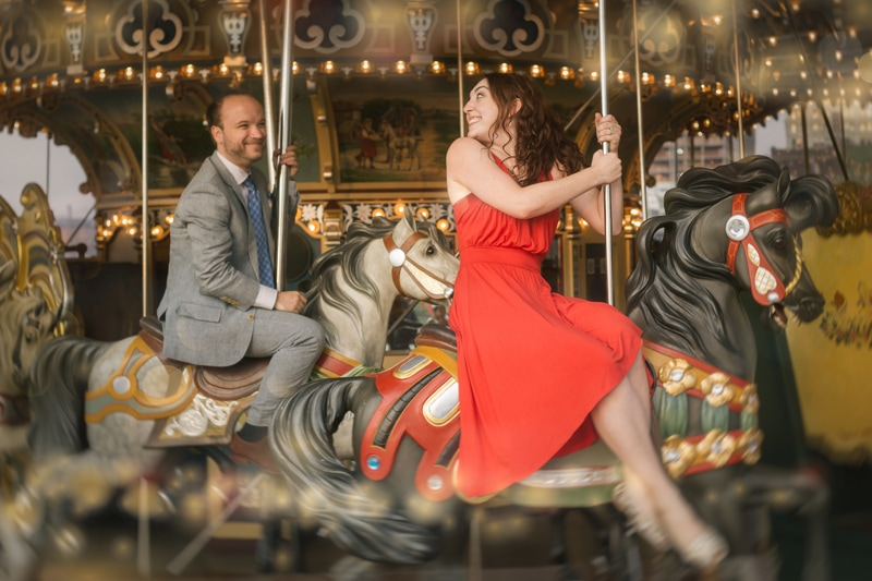 Couples Photography, couple riding a carousel looking at eachother