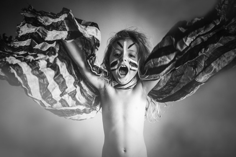 Children and Senior Photography, child pretending to fly with a blanket and face paint