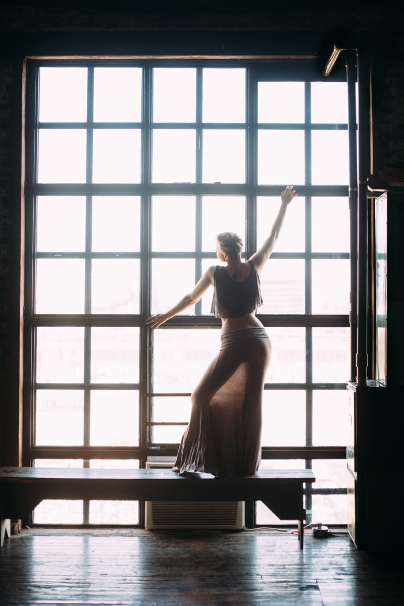 artist photography, woman posing in front of window with a long skirt on