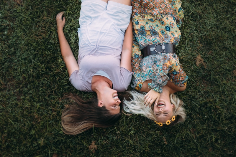 family photography, young ladies laughing and laying in the grass