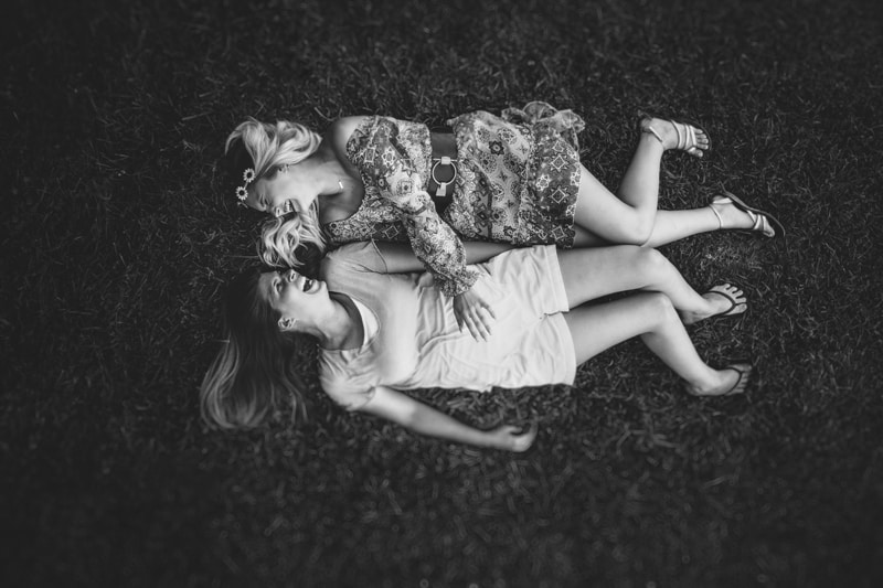 family photography, black and white of young ladies laughing and laying in the grass