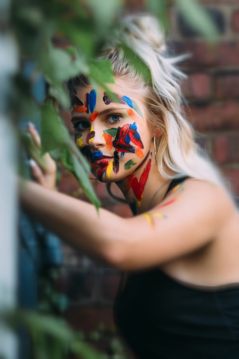 Children and Senior Photography, senior girl leaning against a brick wall with paint on her face