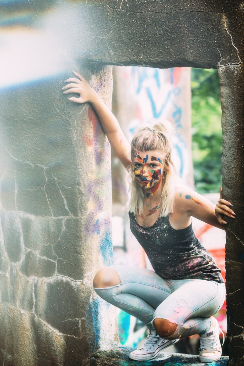 Children and Senior Photography, senior girl crouching down in a stone windowsill with paint on her face