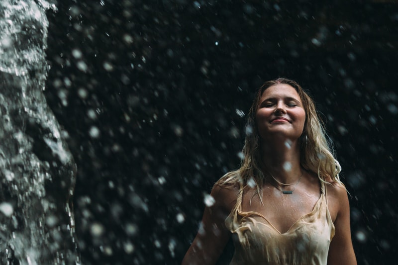 Children and Senior Photography, senior girl standing under waterfall and looking up with her eyes closed
