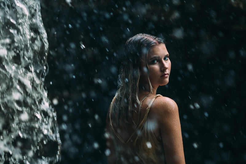 Children and Senior Photography, senior girl looking back over her shoulder under waterfall