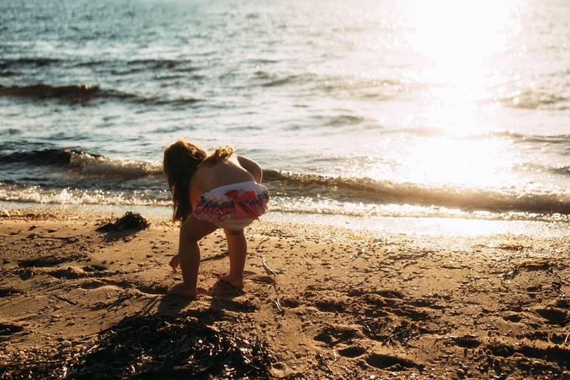 Children and Senior Photography, little girl picking up shells at the beach