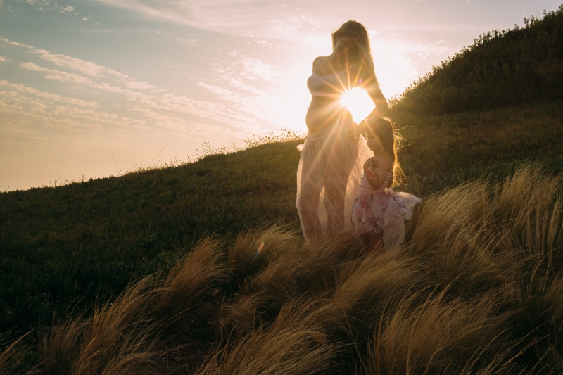 Motherhood and Maternity Photography, mother and daughter standing in tall grass with sunset behind them