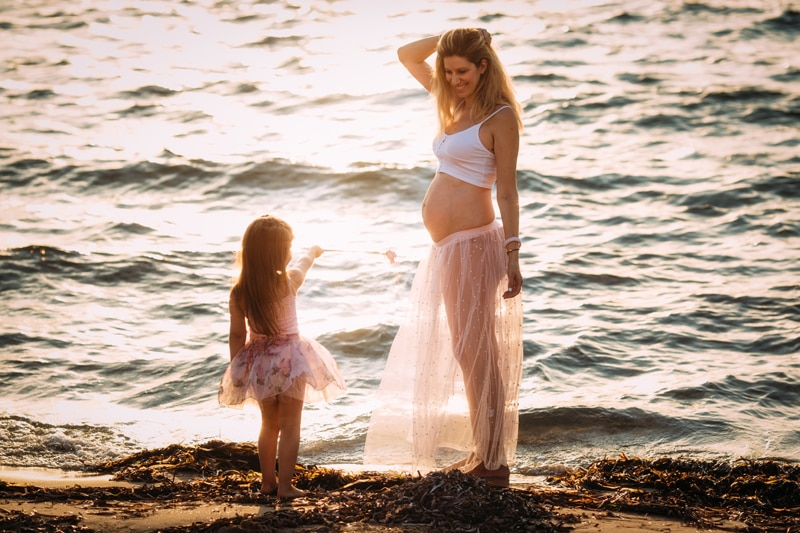 Motherhood and Maternity Photography, pregnant mother standing next to the ocean with young daughter