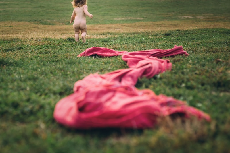 Children and Senior Photography, little naked baby running from the camera in grass field