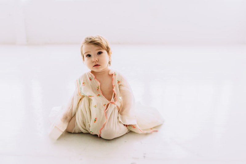 Children and Senior Photography, little girl draped in a flowy top sitting on white floor
