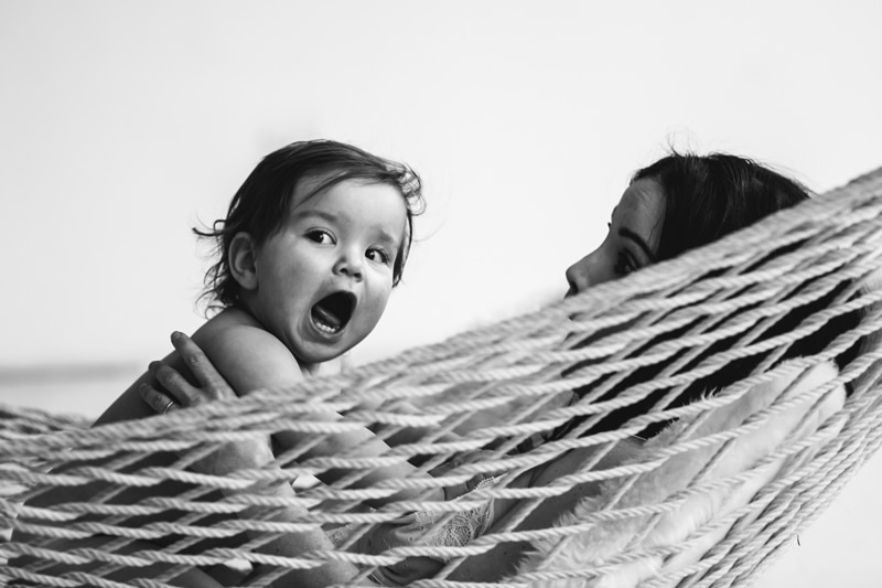 Motherhood and Maternity Photography, black and white image of mother and baby sitting together in a hammock