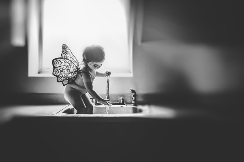 Children and Senior Photography, little girl playing in kitchen sink with butterfly wings on