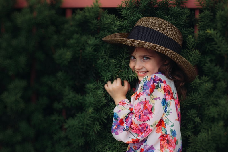 Children and Senior Photography, little girl looking shyly at the camera with hat on